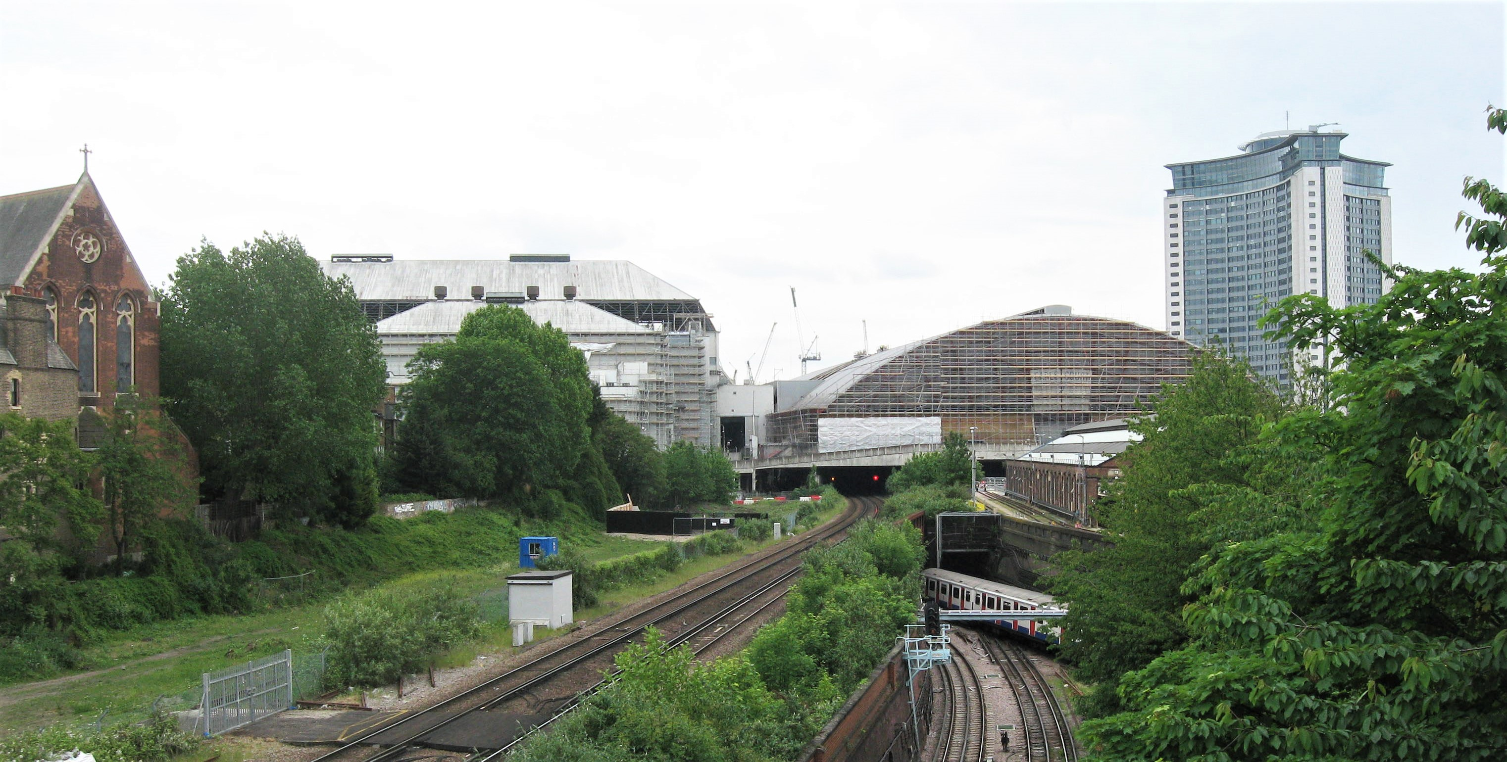 Earl's Court Demolition in progress, general view from Cromwell Road Flyover in June 2015 with original 1936 'Earl's Court 1' on left and 1990 'Earl's Court 2' on right, both sheeted for demolition