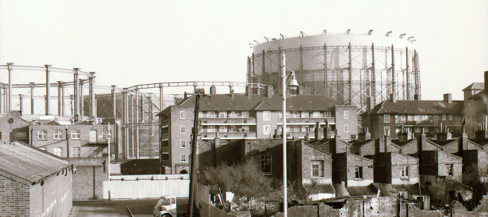 Kennington Oval gas holders in use, Jan 1975. From left, part of frames of 4 and 5; frameless 2, raised but obscured, behind; frame of 3, since demolished; full 1, 'flying' above the frame
